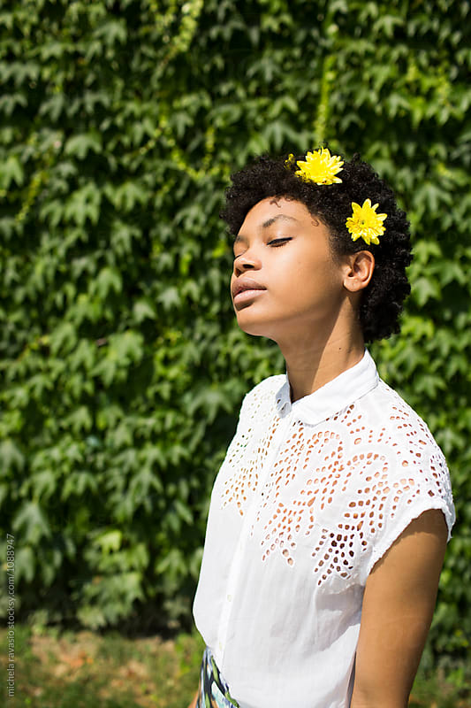 Beautiful girl with yellow flowers in hair enjoying the sun by michela ravasio for Stocksy United
