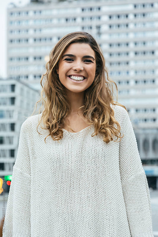 Happy Young Woman Laughing in the Street by Victor Torres for Stocksy United