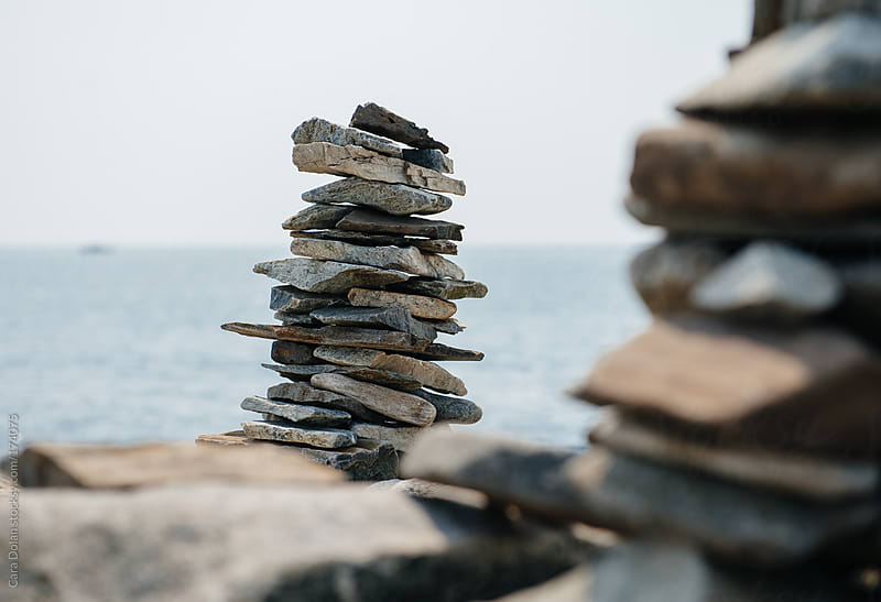 Stacks of flat rocks stand overlooking the ocean by Cara Dolan for Stocksy United