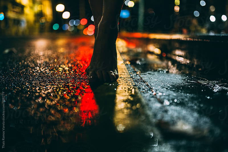 feet on wet road at night by Thais Ramos Varela for Stocksy United
