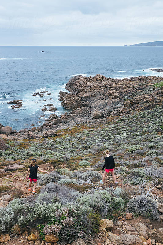 Two girls walking down a hill, over a bush terrain, toward the ocean by Jacqui Miller for Stocksy United