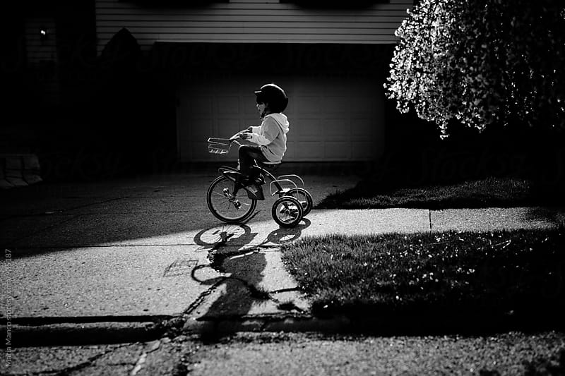 young boy rides tricycle on sidewalk by Maria Manco for Stocksy United