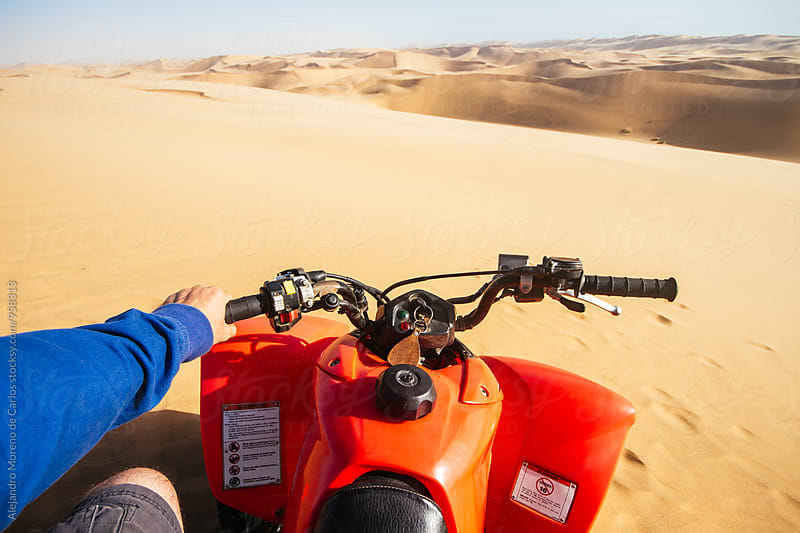 Man steering transport in dunes by Alejandro Moreno de Carlos for Stocksy United