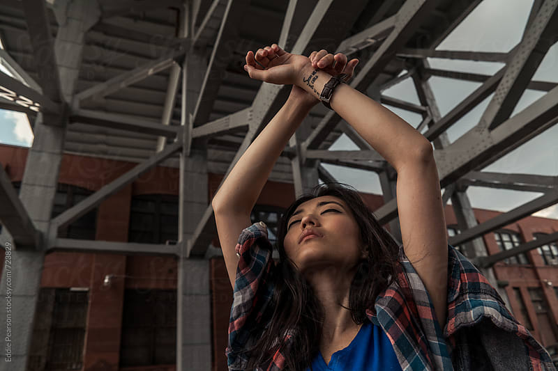 Young woman raising her hands in the air by Eddie Pearson for Stocksy United