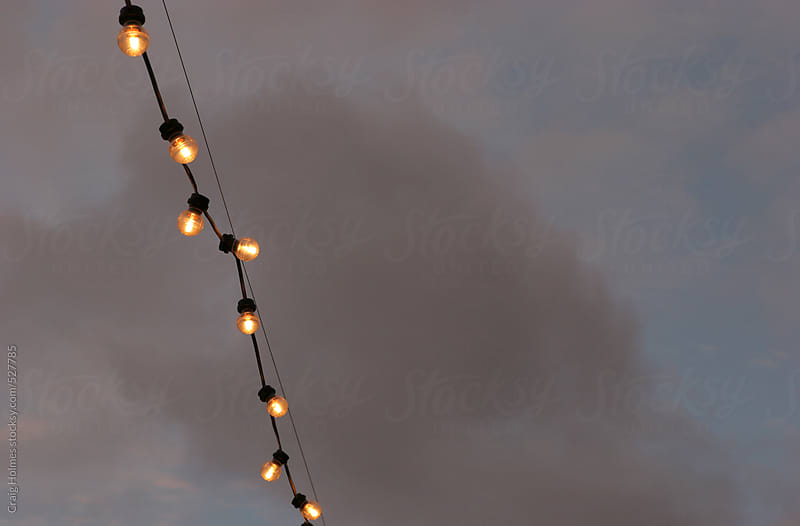 Street celebration lights against a stormy sky by Craig Holmes for Stocksy United