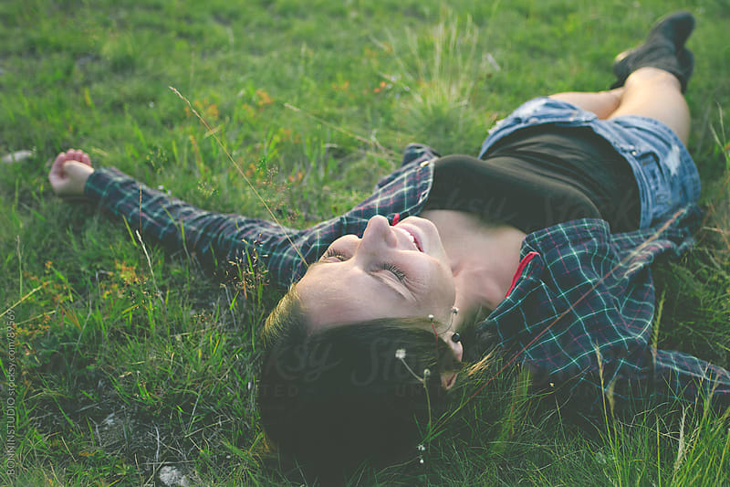 Smiling woman lying on green grass with stretched arms and legs. by BONNINSTUDIO for Stocksy United