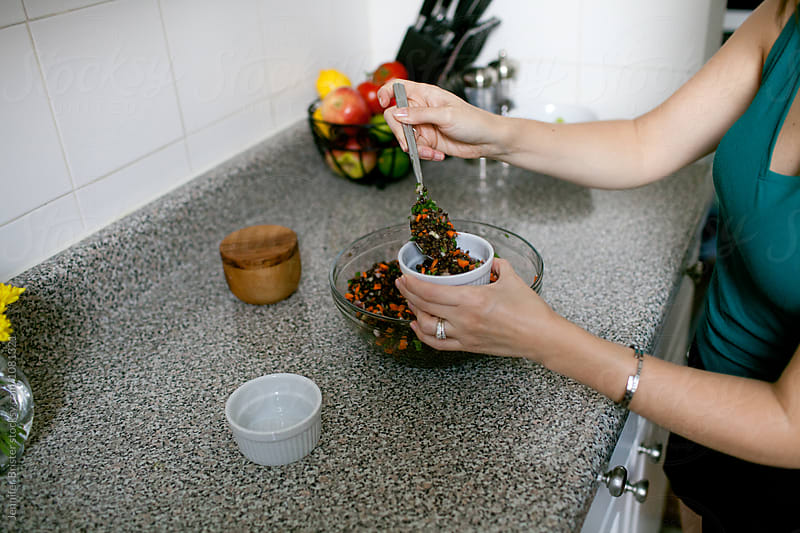 Woman spoons salad into small bowl  by Jennifer Brister for Stocksy United