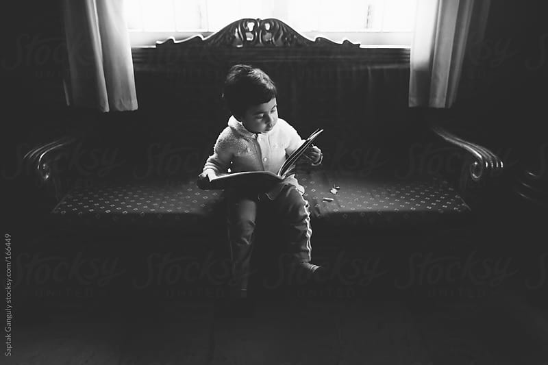 Toddler reading magazine sitting on a sofa by Saptak Ganguly for Stocksy United