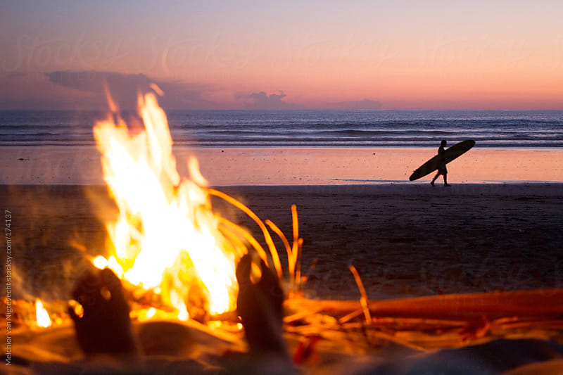 Fire on the beach with sunset and surfer on the background by Melchior van Nigtevecht for Stocksy United
