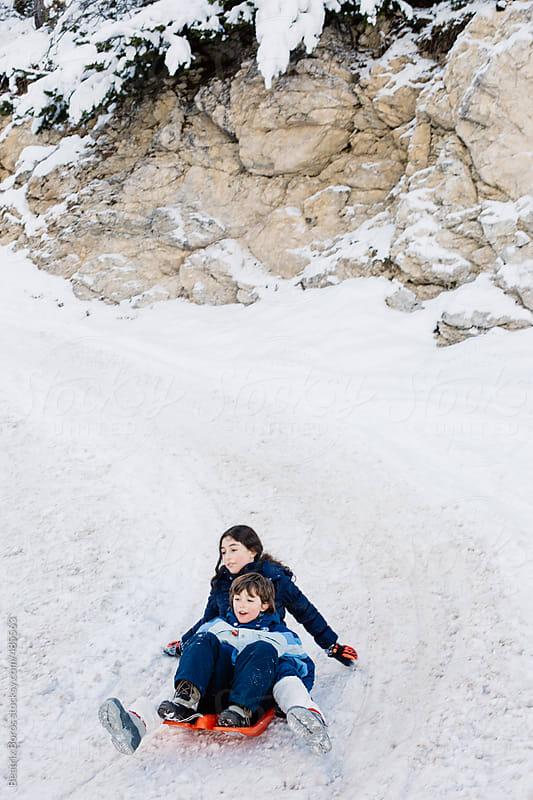 Siblings sledding downhil by Beatrix Boros for Stocksy United