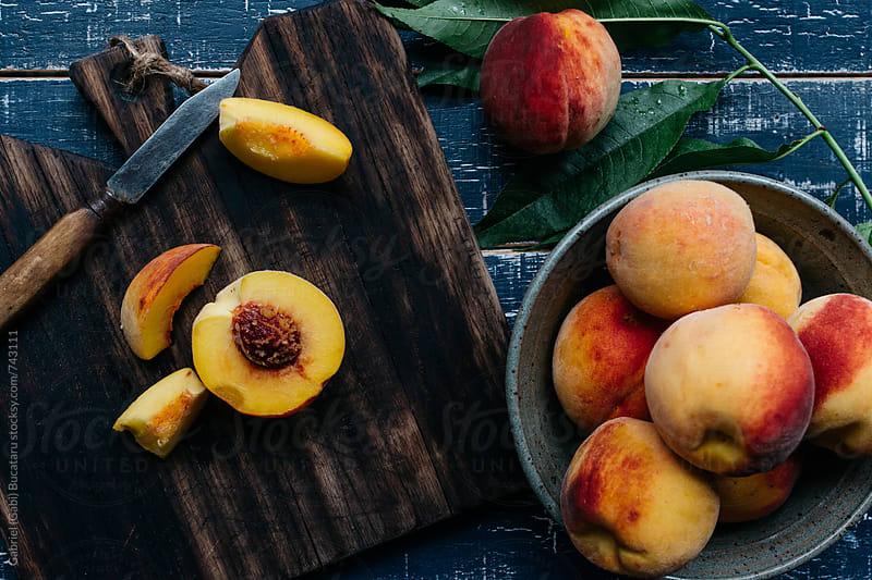 Fresh peaches on a chopping board from above by Gabriel (Gabi) Bucataru for Stocksy United
