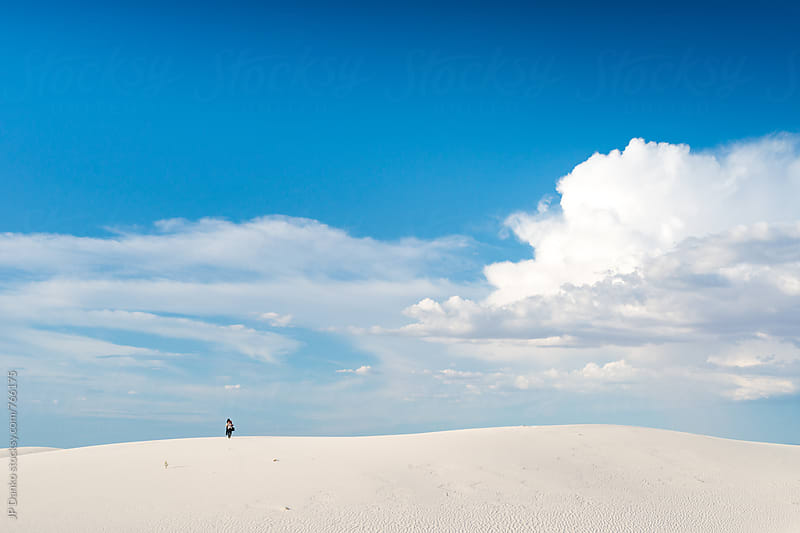 Man Approaching From Horizon Carrying Camping and Photography Gear in White Sands National Monument New Mexico by JP Danko for Stocksy United