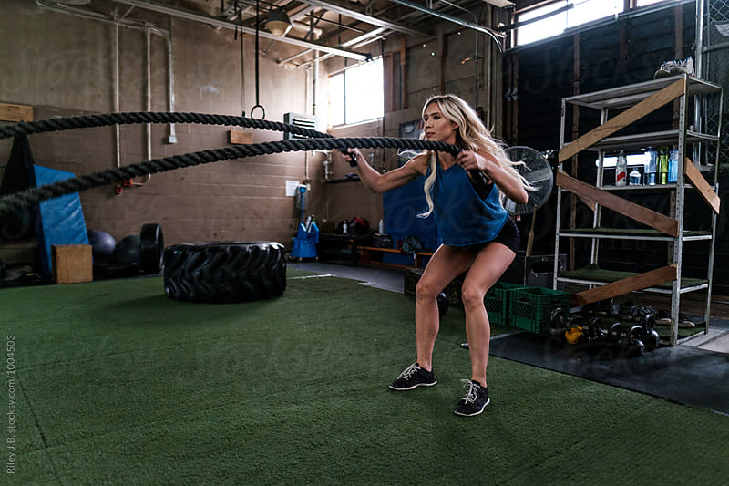An attractive woman using battling ropes in gritty gym by Riley Joseph for Stocksy United