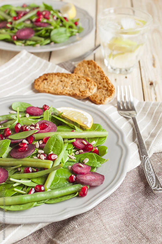 Fresh salad with spinach, violet carrot, pomegranate seeds and sunflower seeds by Nataša Mandić for Stocksy United