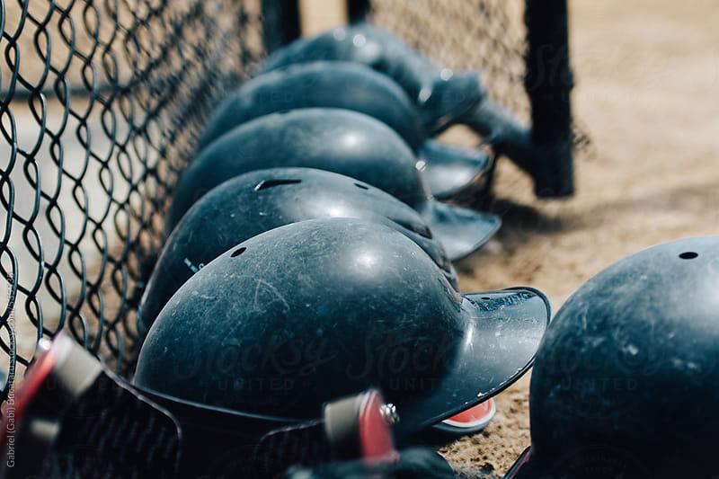 Baseball helmets by a wire fence by Gabriel (Gabi) Bucataru for Stocksy United