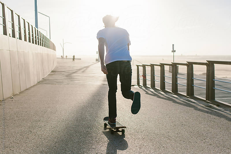 Man skateboarding along the beach by Denni Van Huis for Stocksy United
