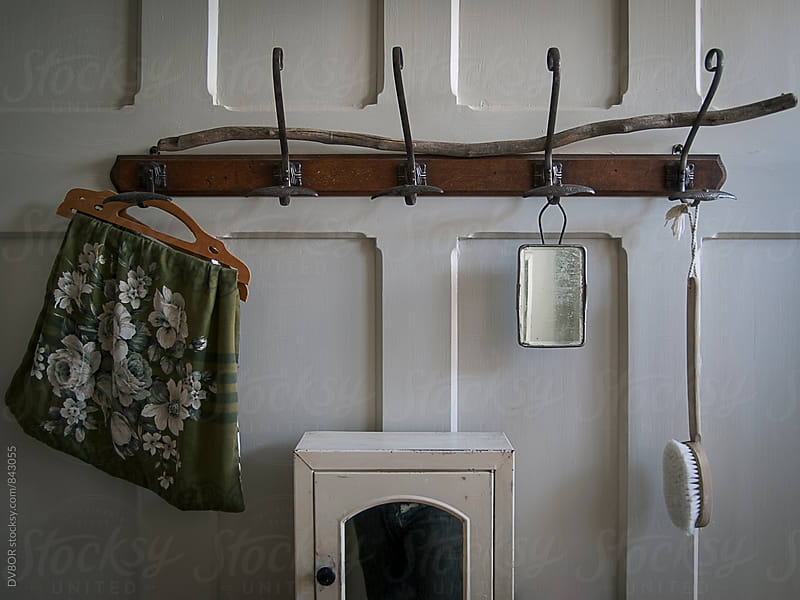Interior of a Hipster Vintage decorated bathroom in England with wood panelled wall and coat hooks by DV8OR for Stocksy United
