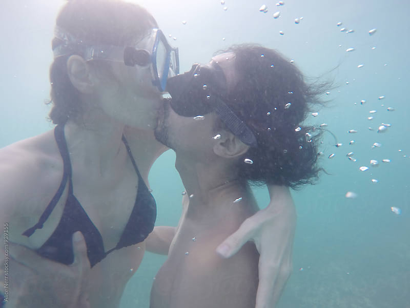 Couple in scuba masks kissing underwater by Alice Nerr for Stocksy United