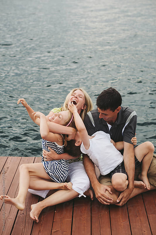 Young family hugging together on the dock at the lake by Rob and Julia Campbell for Stocksy United