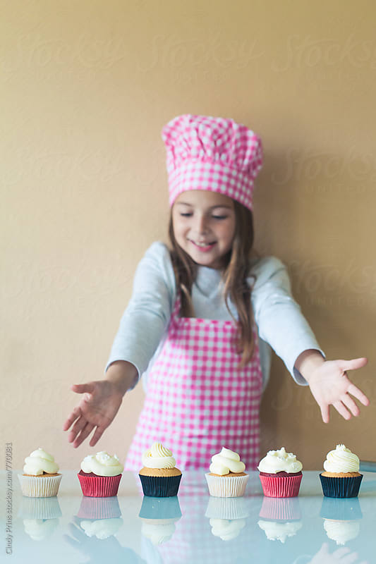 Little girl in apron showing her freshly baked cupcakes by Cindy Prins for Stocksy United
