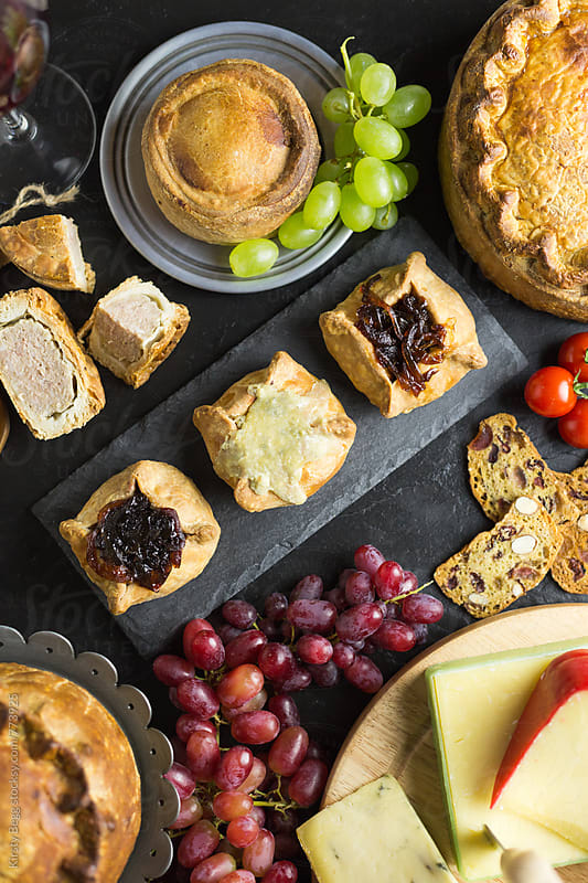 Cheese and pickle topped pork pies with cheese selection by Kirsty Begg for Stocksy United