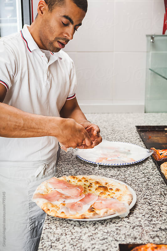 Adding Prosciutto Crudo Ham on a Focaccia Pizza by Giorgio Magini for Stocksy United