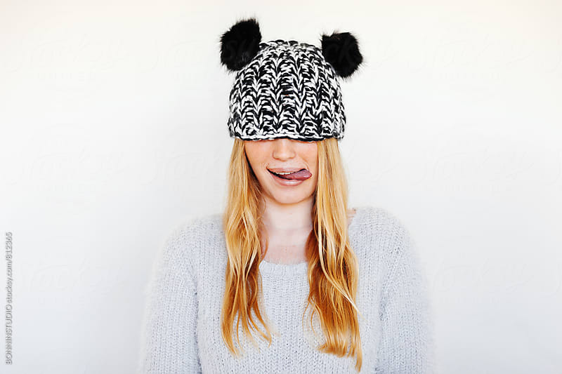 Funny portrait of a blonde woman wearing a winter wool hat. by BONNINSTUDIO for Stocksy United