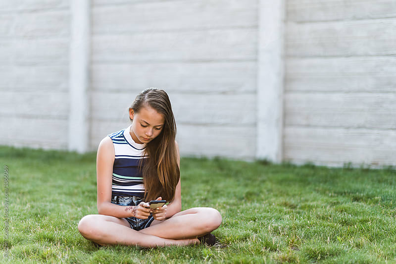 Teen Girl On Cell Phone Outdoors by Ronnie Comeau for Stocksy United