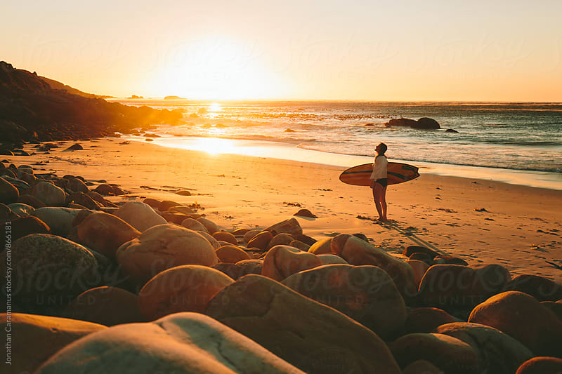 Young woman surfer with surfboard standing on beach at sunset by Jonathan Caramanus for Stocksy United