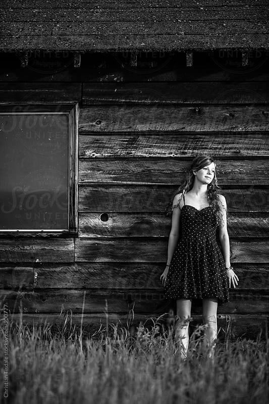 Black and white of young girl wearing a dress leaning against a rustic barn looking to the right  by Christian Tisdale for Stocksy United