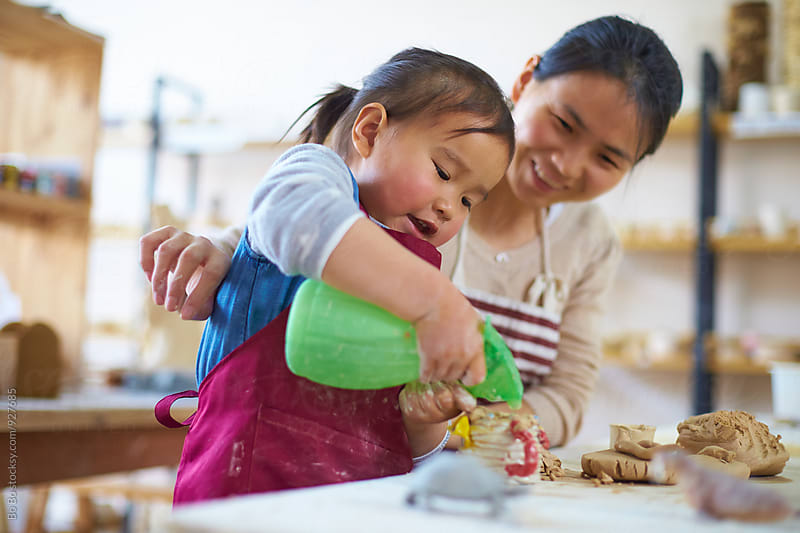 little asian girl busy in the ceramics studio together with her mother by Bo Bo for Stocksy United