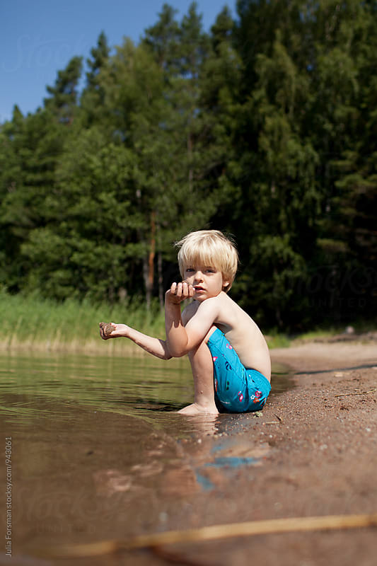 Scandinavian child sitting on a beach with forest behind him. by Julia Forsman for Stocksy United