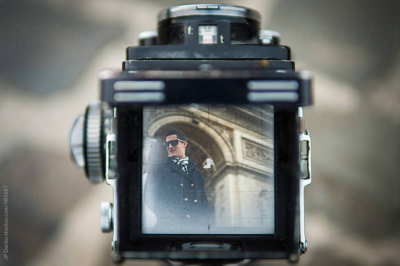 Vintage Film Medium Format Camera Photographing Stylish Man With Arc de Triomphe Paris by JP Danko for Stocksy United