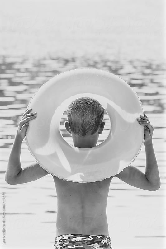 black and white ,a blond boy with a swimming ring enjoying in front of the sea by Igor Madjinca for Stocksy United
