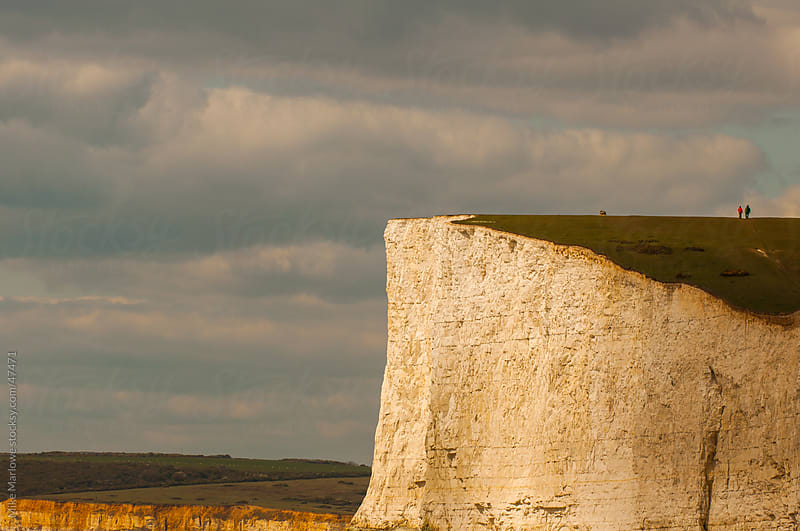 A white cliff face with some distant people on the top by Mike Marlowe for Stocksy United