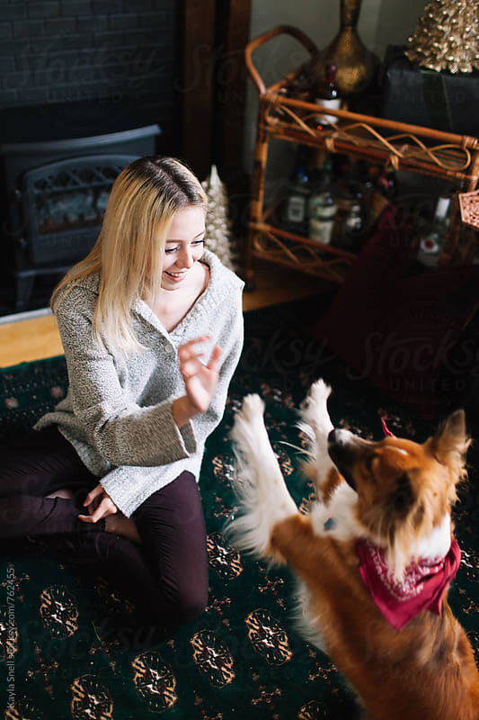 Woman playing with her dog over Christmas break by Kayla Snell for Stocksy United