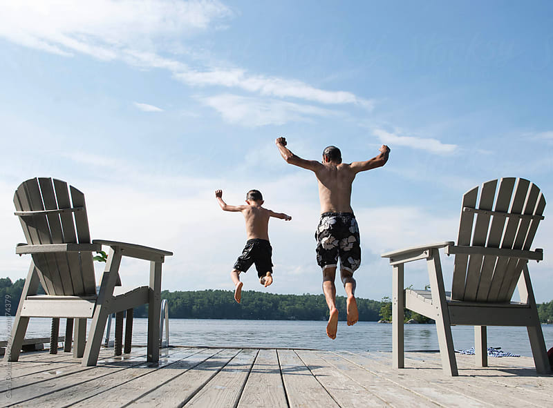 Father and son jump together off a dock into the lake by Cara Slifka for Stocksy United