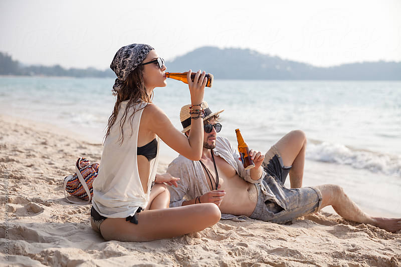 Couple enjoying summer day at the beach drinking beer by Jovo Jovanovic for Stocksy United