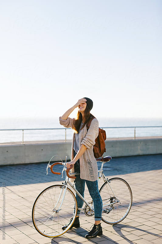 Smiling woman covering her eyes and standing with her vintage bicycle. by BONNINSTUDIO for Stocksy United