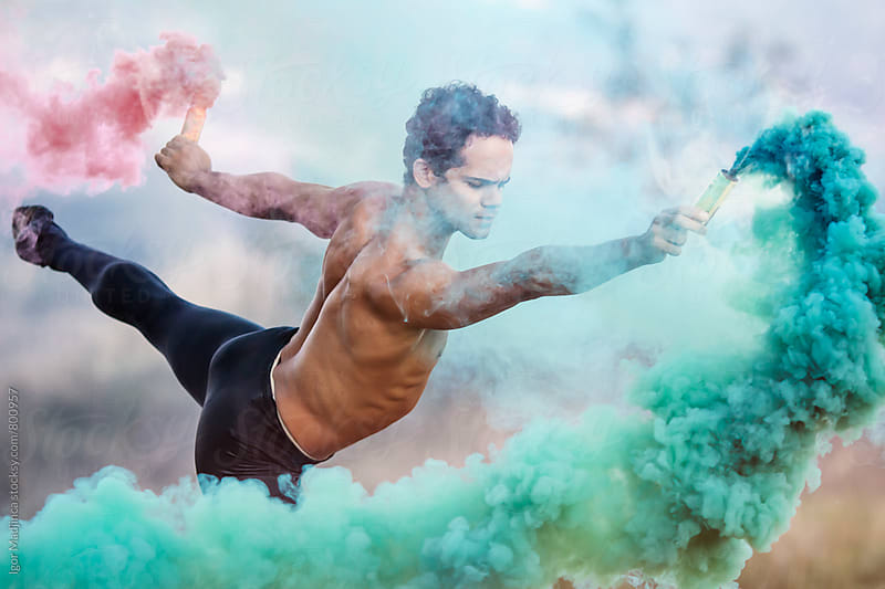 colorful,ballet dancer with two smoke bombs dance in nature by Igor Madjinca for Stocksy United