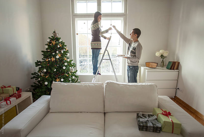 Young Couple Decorating Home for Christmas by Mosuno for Stocksy United