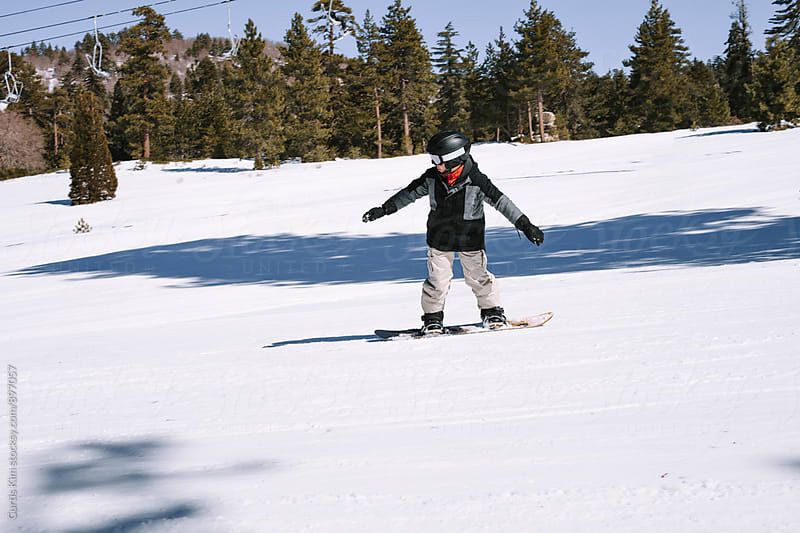 Young snowboarder riding snowboard  by Curtis Kim for Stocksy United