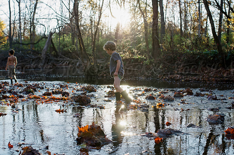 Boy in a Creek by Ali Deck for Stocksy United