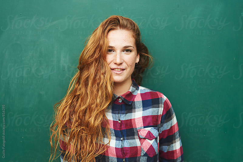 Portrait of red-haired young woman looking at camera by Guille Faingold for Stocksy United