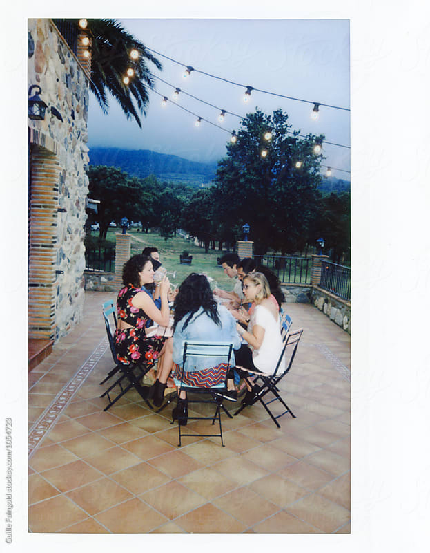 Instant shot of friend having dinner on veranda in countryside by Guille Faingold for Stocksy United