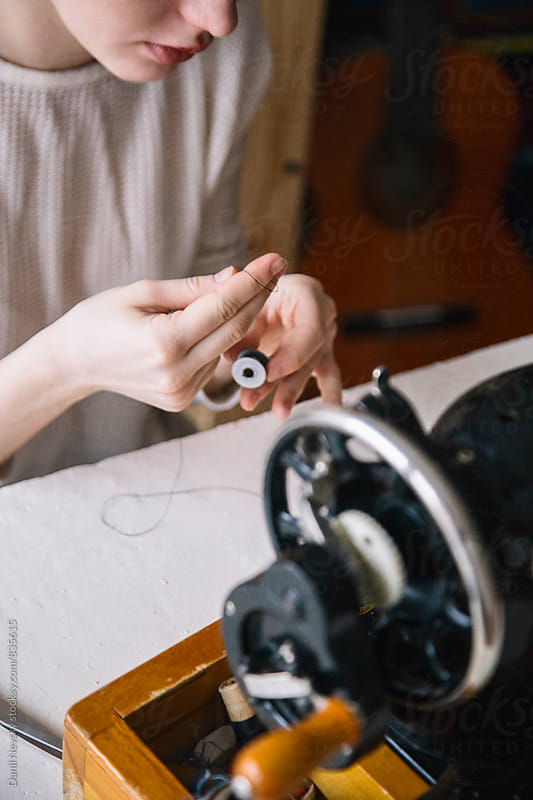 Woman changing bobbin in vintage sewing machine by Danil Nevsky for Stocksy United