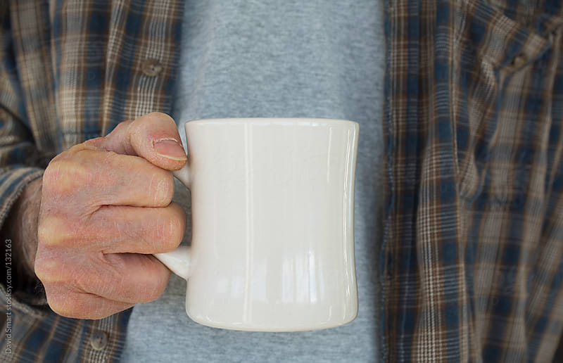 Man in casual clothes holding a white coffee mug by David Smart for Stocksy United