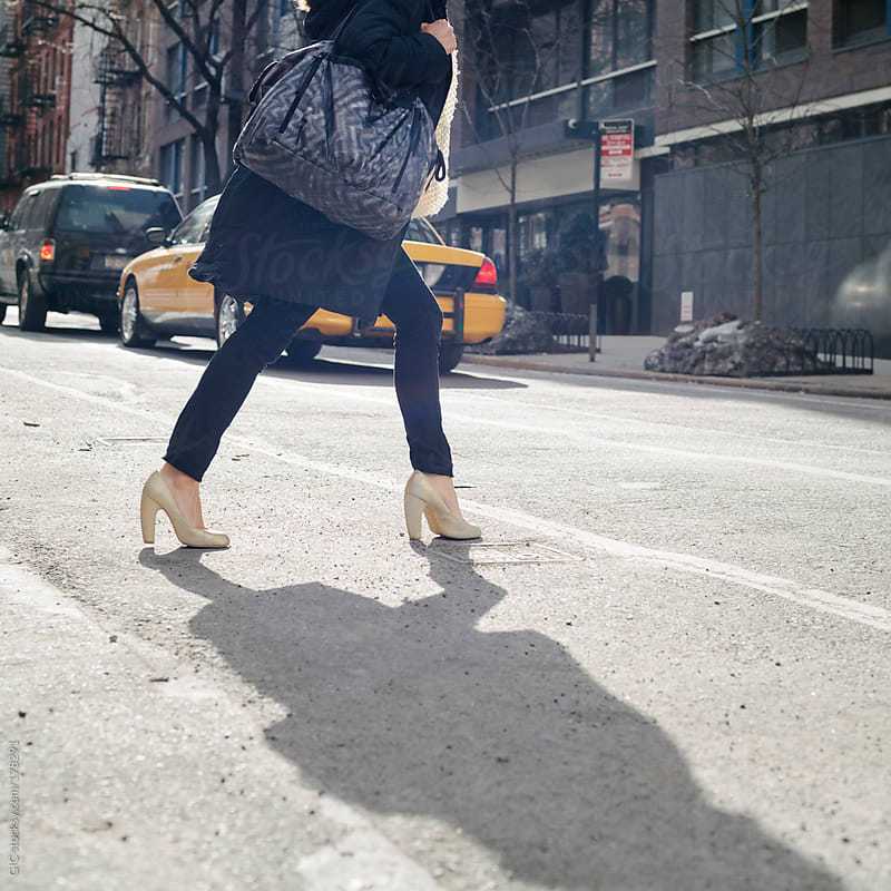 Woman crossing the street in New York City by GIC for Stocksy United