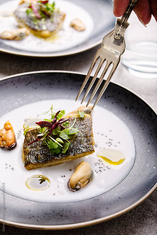 Sea bream with mussel and coconut broth: A fork taking a piece of fish from a plate. by Darren Muir for Stocksy United