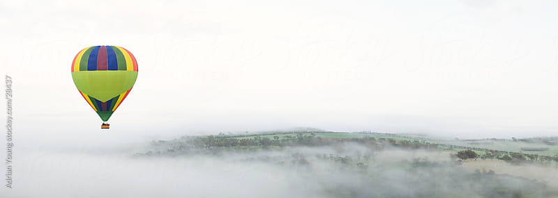 Hot Air Ballooning Above Foggy Hills by Adrian P Young for Stocksy United